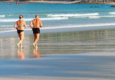 Older couple running on beach